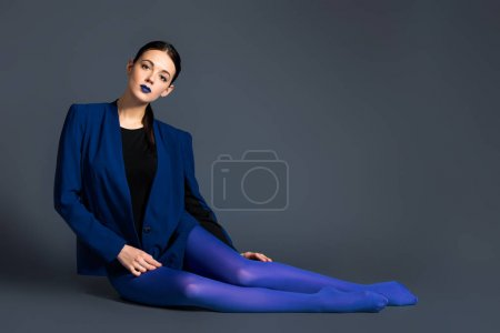 Fashionable woman in blue pantyhose and jacket lying on dark background