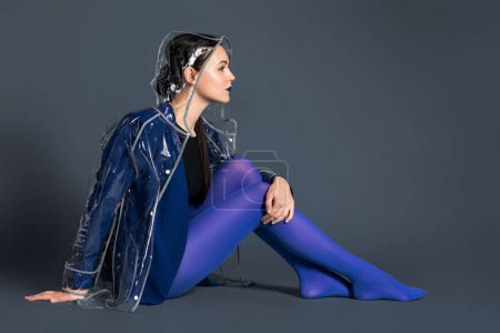 Stylish woman in blue tights and transparent raincoat sitting on dark background
