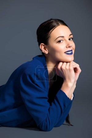 Photo pour Jeune fille souriante avec rouge à lèvres bleu Gilet bleu sur fond foncé - image libre de droit