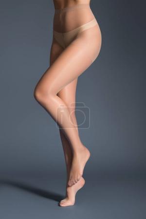 Slim woman in beige tights on dark background