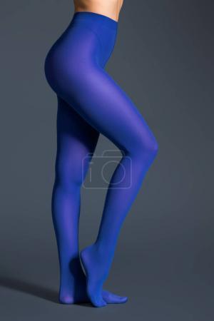 Female legs in blue pantyhose on dark background