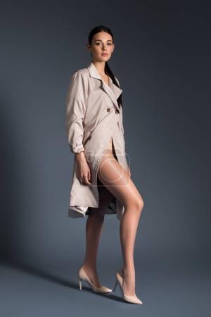 Photo pour Jeune femme portant le trench beige posant sur fond foncé - image libre de droit