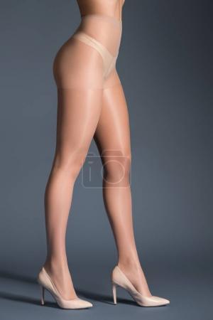 Photo pour Jambes féminines en collants beige et chaussures sur fond sombre - image libre de droit