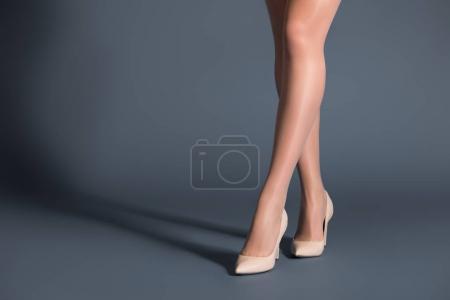 Photo pour Femme portant des collants beiges et des chaussures à talons sur fond sombre - image libre de droit