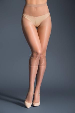 Photo pour Femme séduisante en collants et chaussures beige sur fond sombre - image libre de droit