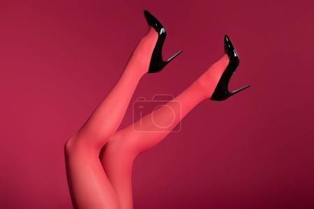 Photo pour Jambes féminines en collants rouges isolés sur rouge - image libre de droit