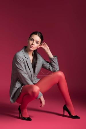 Attractive woman in red pantyhose and grey jacket on red background