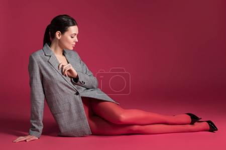 Slim woman in red pantyhose and grey jacket lying on red background