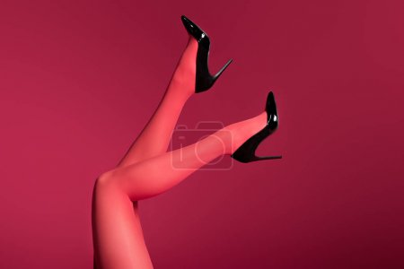 Woman wearing red tights posing isolated on red background