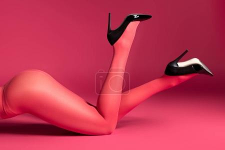 Photo for Woman in red pantyhose and heel shoes lying on red background - Royalty Free Image
