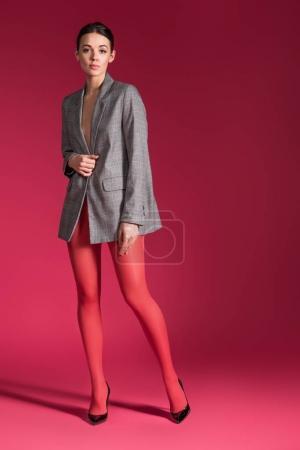 Photo pour Femme sensuelle en collants nylon rouge gilet gris sur fond rouge - image libre de droit