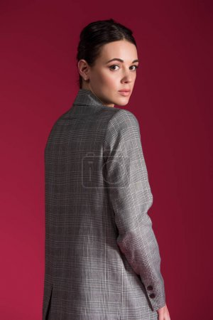 Young woman in grey jacket posing isolated on red background