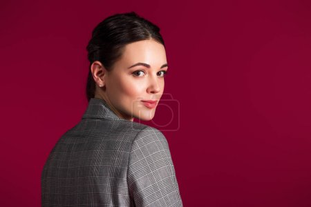 Smiling girl in grey jacket posing isolated on red background