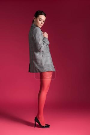 Photo for Woman with thin legs in red nylon tights on red background - Royalty Free Image