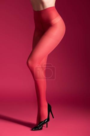Seductive woman in red tights and shoes on red background