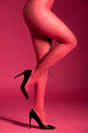 Photo for Woman posing in red pantyhose and heel shoes on red background - Royalty Free Image