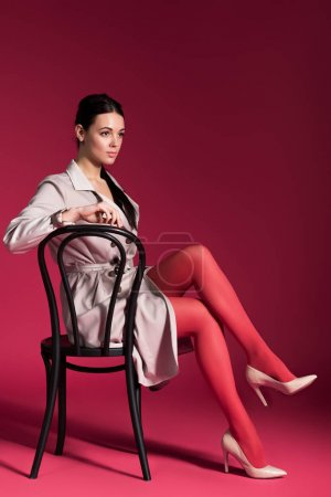 sexy woman in red pantyhose and beige trench sitting on chair on red background