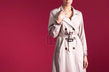 Stylish woman in beige trench isolated on red background