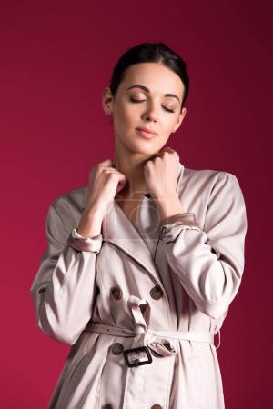 Photo pour Fille rêveuse portant tranchée beige isolé sur fond rouge - image libre de droit
