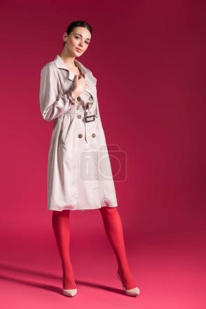 Smiling girl wearing beige trench and high heels on red background