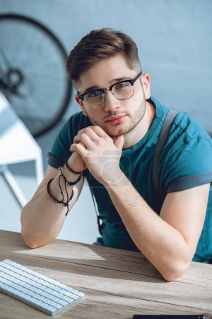 handsome young man in eyeglasses looking at camera while working at home