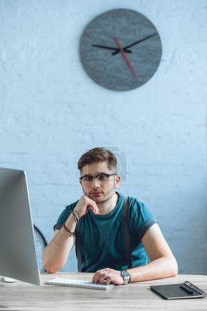 handsome young freelancer in eyeglasses using desktop computer at home office