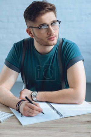Photo pour Cher jeune homme dans les lunettes détourner les yeux tout en écrivant dans un cahier - image libre de droit