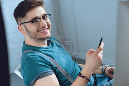 cheerful young man using smartphone and smiling at camera