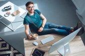 vue de la forte inclinaison du beau jeune homme à lunettes, souriant à la caméra en position assise au milieu de travail à la maison, Bureau
