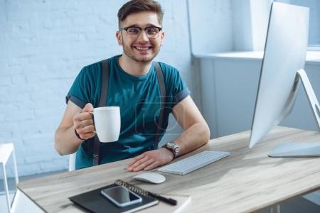 Photo pour Beau jeune homme tenant tasse et souriant à la caméra tout en travaillant avec ordinateur de bureau - image libre de droit