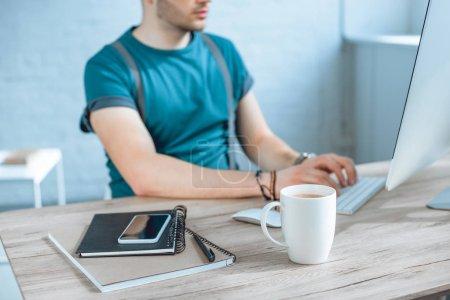 Photo pour Vue rapprochée du smartphone, ordinateurs portables et tasse de café, pigiste travaillant derrière - image libre de droit