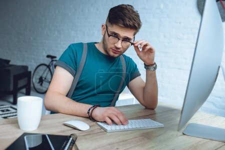 handsome young freelancer adjusting eyeglasses and looking at camera while working with desktop computer