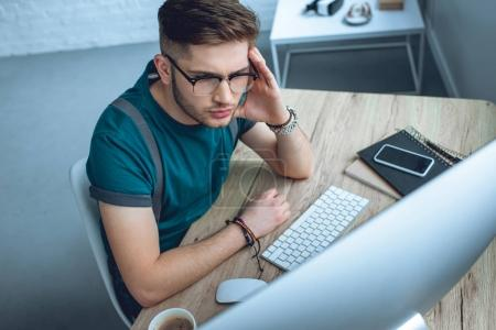 high angle view of concentrated young man in eyeglasses working with desktop computer at home office