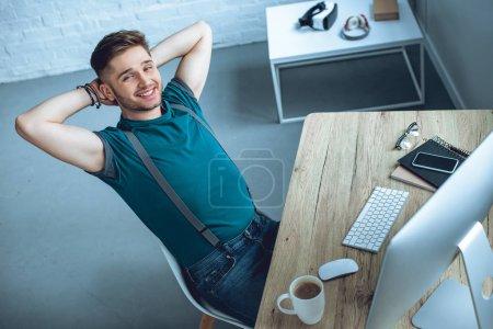 Photo pour Vue grand angle de beau jeune pigiste assis avec les mains derrière la tête et souriant à la caméra - image libre de droit