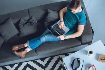Photo pour Vue aérienne du jeune homme travaillant avec un ordinateur portable assis sur le canapé à la maison - image libre de droit