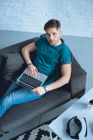 high angle view of handsome young man using laptop and looking at camera