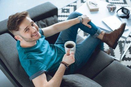 vista de ángulo alto de joven guapo bebiendo café y sonriendo a la cámara en casa