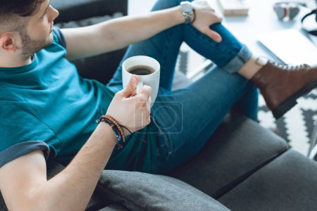 cropped shot of stylish young man holding cup of coffee and sitting on couch