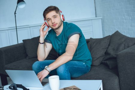 handsome young man in headphones looking at camera while working with laptop at home