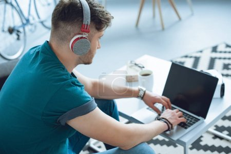 Photo for Young man in headphones using laptop at home - Royalty Free Image