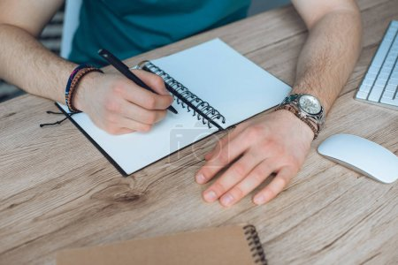 cropped shot of young man taking notes in blank notebook