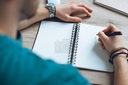 selective focus of young man taking notes in blank notebook