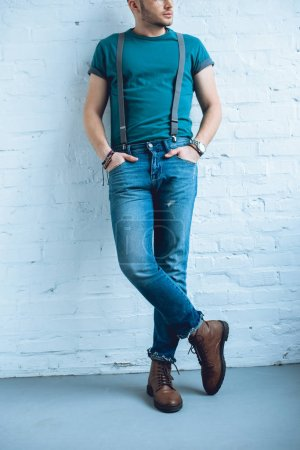 Attractive young man wearing jeans with suspenders