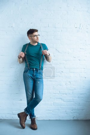 Handsome young man wearing wearing jeans with suspenders and standing by white wall
