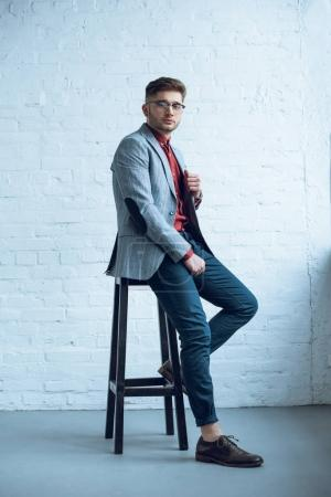 Handsome young man wearing suit sitting on tall chair