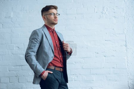 Photo for Stylish man in casual clothes wearing glasses by brick wall - Royalty Free Image