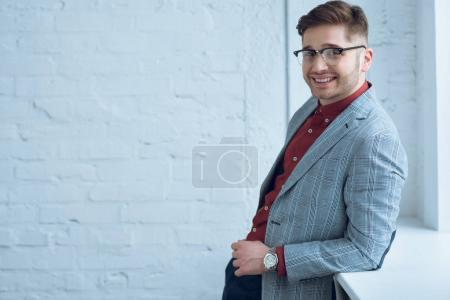 Photo for Smiling stylish man in casual clothes leaning on windowsill - Royalty Free Image