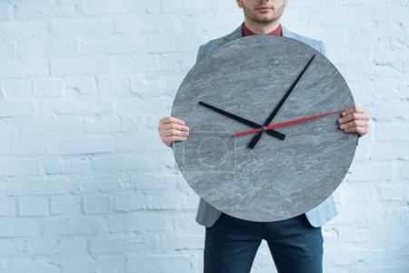 Photo pour Jeune homme tenue grande horloge devant lui en se tenant par le mur de briques - image libre de droit