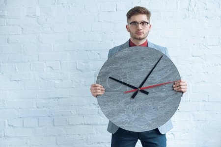 Man holding large clock in front of him by white wall