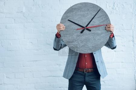 Large clock in male hands by brick wall